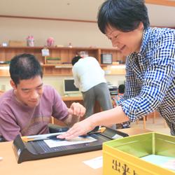 作業をする利用者さんとその支援を行うスタッフの写真
