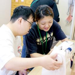 ミシンで作業を行う利用者さんとその支援をするスタッフの写真