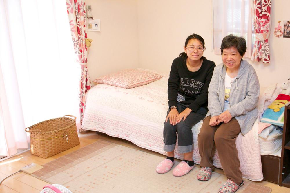 グループホームの一室にて、ベッドに腰掛ける利用者さんとスタッフの様子