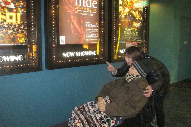 映画館でポスターを眺める利用者さんとスタッフの様子