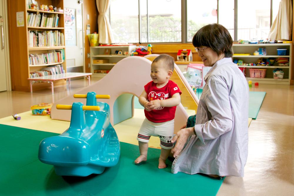 遊具で遊ぶ子供とその祖母の写真